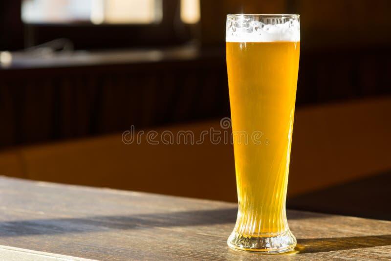 Zonovergoten Glas Bier op Lijst stock foto's