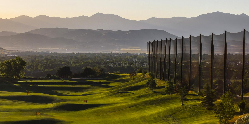 Zonovergoten golfcursus met een omheining aan één kant royalty-vrije stock afbeeldingen