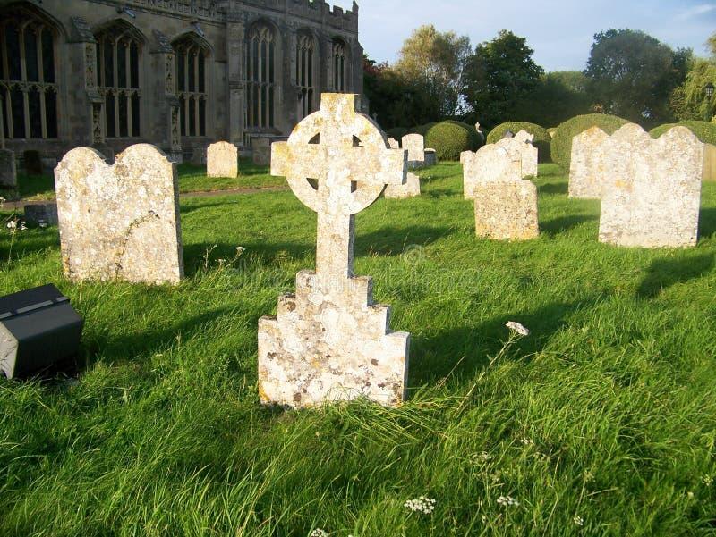 Zonovergoten grafstenen in oude begraafplaats stock foto's