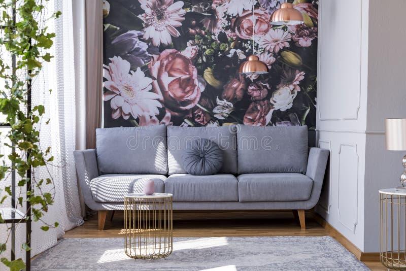 Zonovergoten, grijze bank door een bloemendrukmuur in het hoekje van een femini stock afbeelding