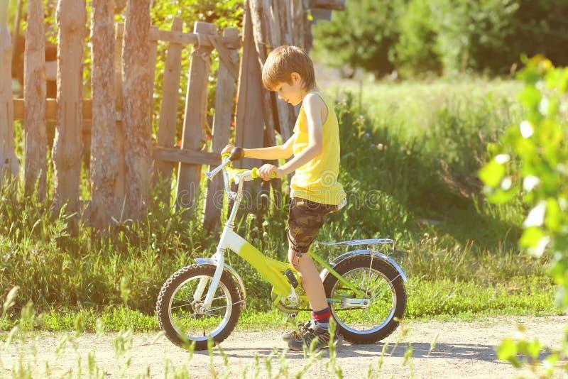 Zonovergoten profielportret van zes éénjarigen jongen het leren om een fiets te berijden stock fotografie
