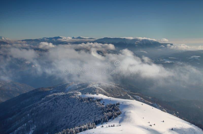 Zonovergoten randen van Velka Fatra en Nizke Tatry boven de wolken stock afbeelding