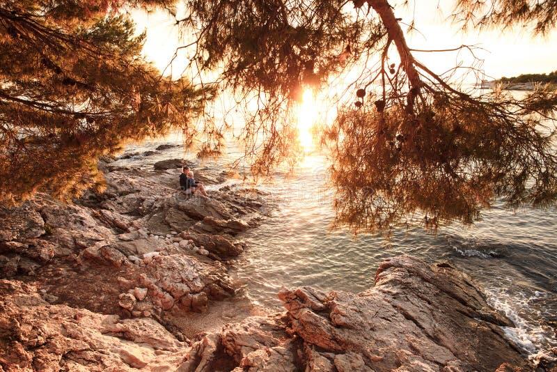 Zonovergoten strand bij zonsondergang met moeder en zoonszitting op kust royalty-vrije stock afbeeldingen