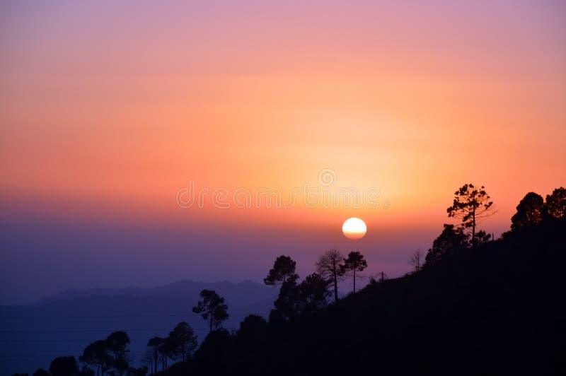 Zonsondergang aan heuvelkant stock afbeeldingen