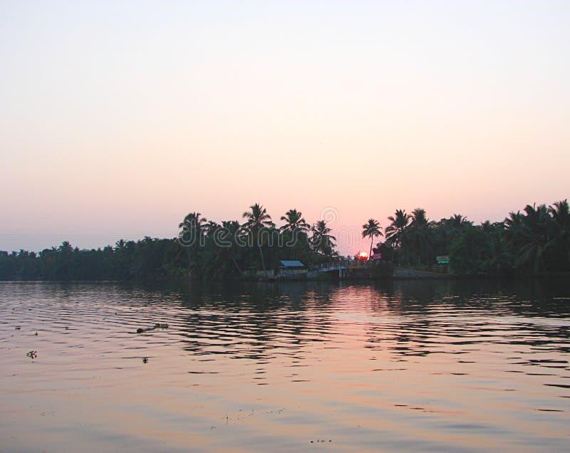 Zonsondergang achter Bomen over Binnenwater, Kerala, India royalty-vrije stock afbeelding