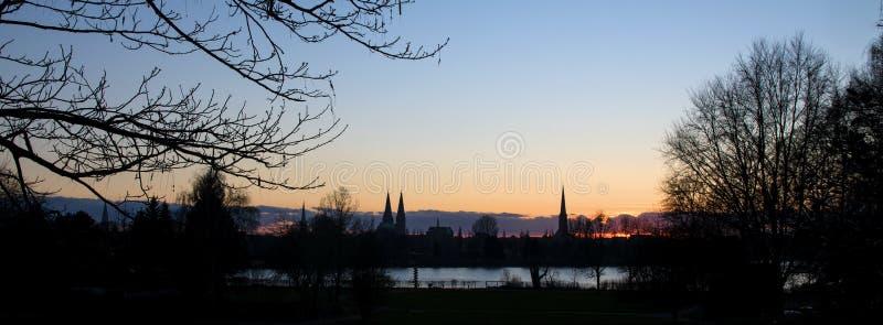 Zonsondergang achter de kerktorens van Luebeck, noordelijk Duitsland royalty-vrije stock foto