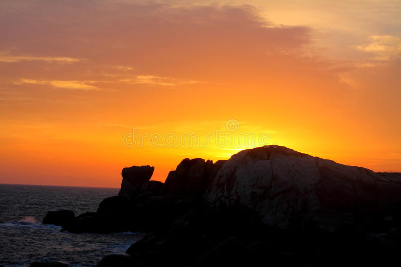 Zonsondergang achter rotsen stock afbeelding