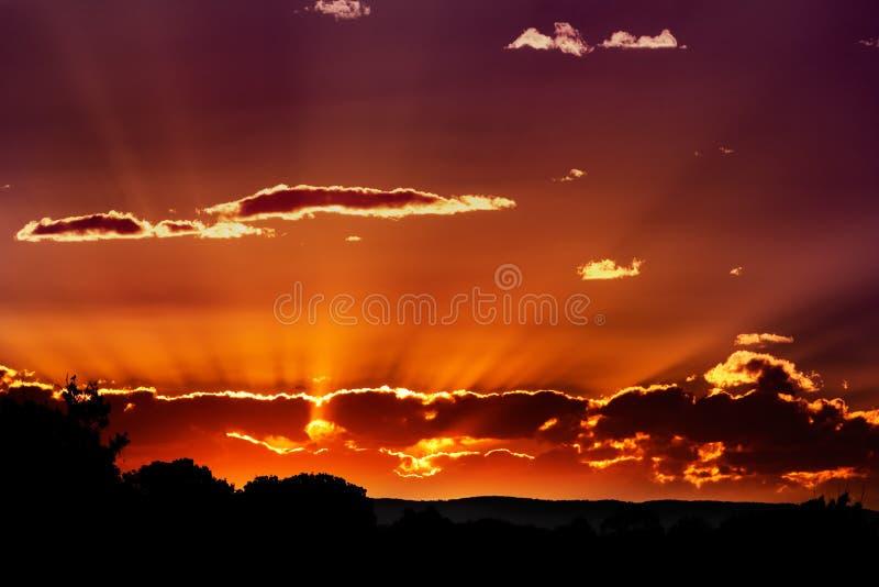 Zonsondergang achter wolken stock afbeelding