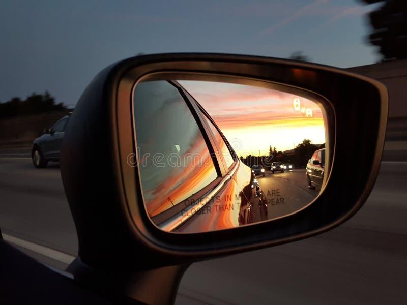 Zonsondergang in autospiegel stock foto's