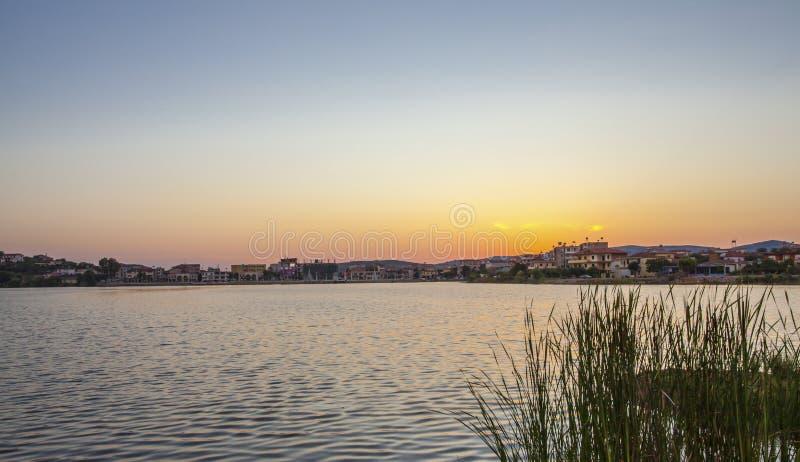 Zonsondergang bij de meer en stadshorizon op de achtergrond Albanië stock foto
