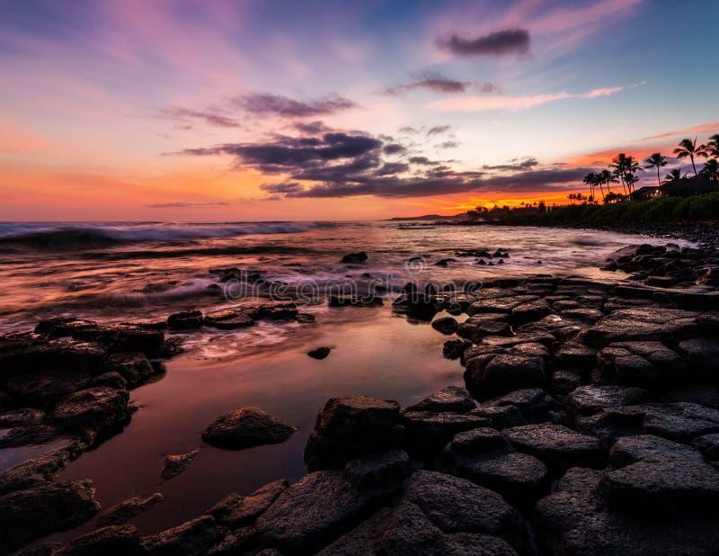Zonsondergang bij een rotsachtig strand royalty-vrije stock afbeeldingen