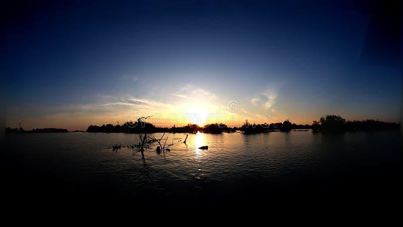 Zonsondergang bij het overzees met toneelwolken op de horizon royalty-vrije stock afbeelding