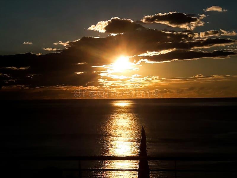 Zonsondergang bij het overzees met toneelwolken op de horizon stock afbeeldingen