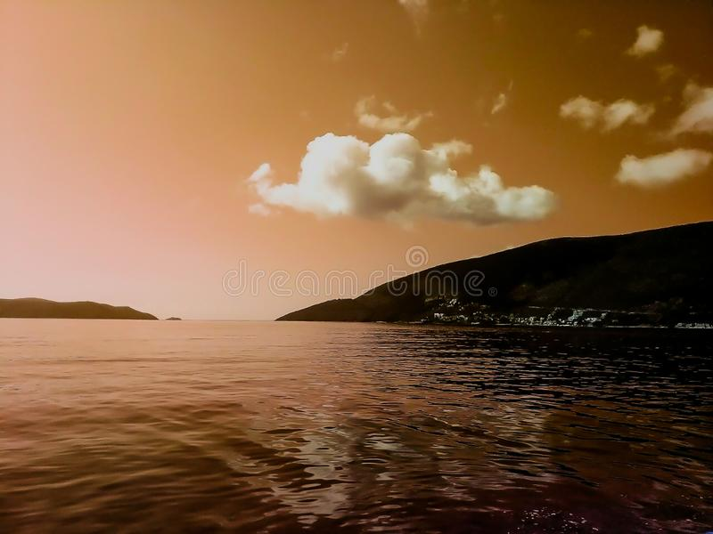 Zonsondergang bij het overzees met toneelwolken op de horizon stock foto's