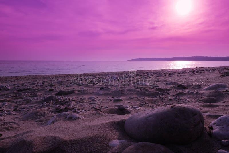 Zonsondergang bij het rotsachtige strand royalty-vrije stock afbeelding