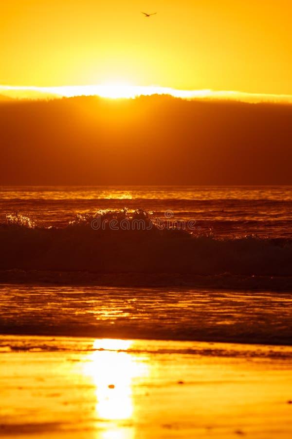 Zonsondergang bij het strand met golven royalty-vrije stock foto