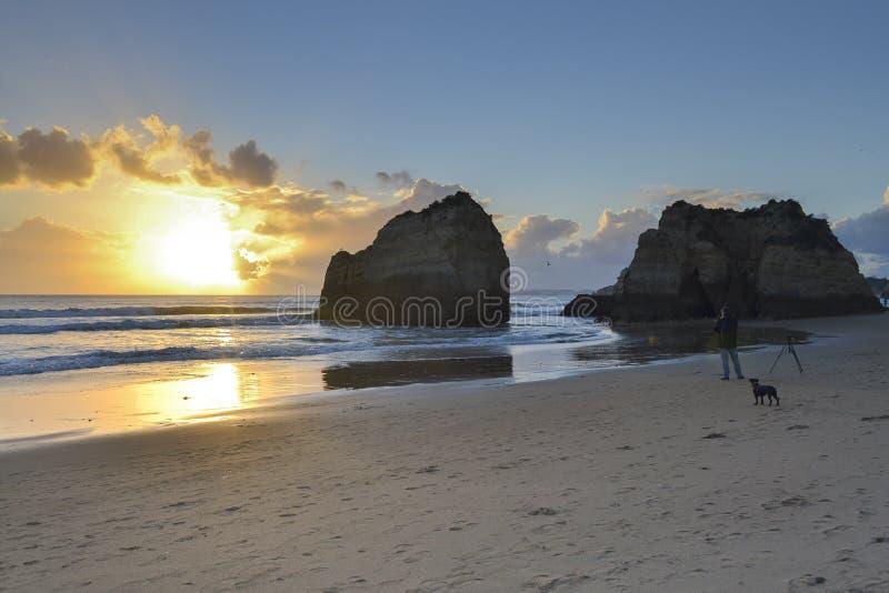 Zonsondergang bij het strand met rotsen royalty-vrije stock foto's