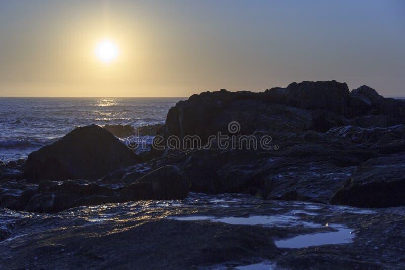 Zonsondergang bij het strand met sommige kustrotsen royalty-vrije stock afbeelding