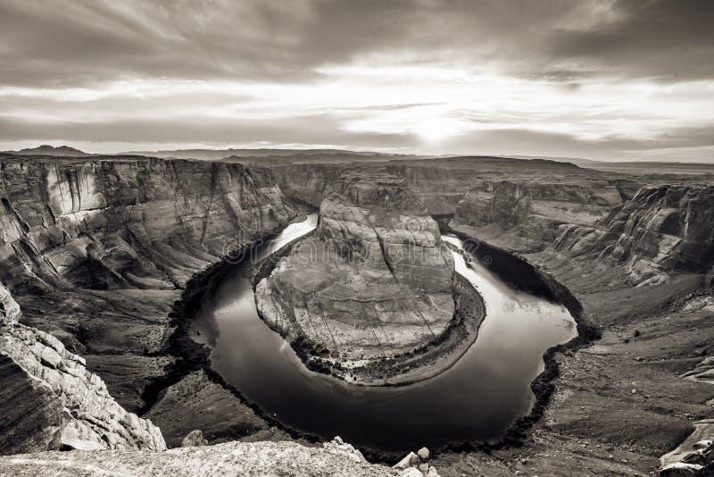 Zonsondergang bij HoefijzerdieKromming - Grand Canyon met de Rivier van Colorado - in Pagina, Arizona, de V.S. wordt gevestigd stock foto's
