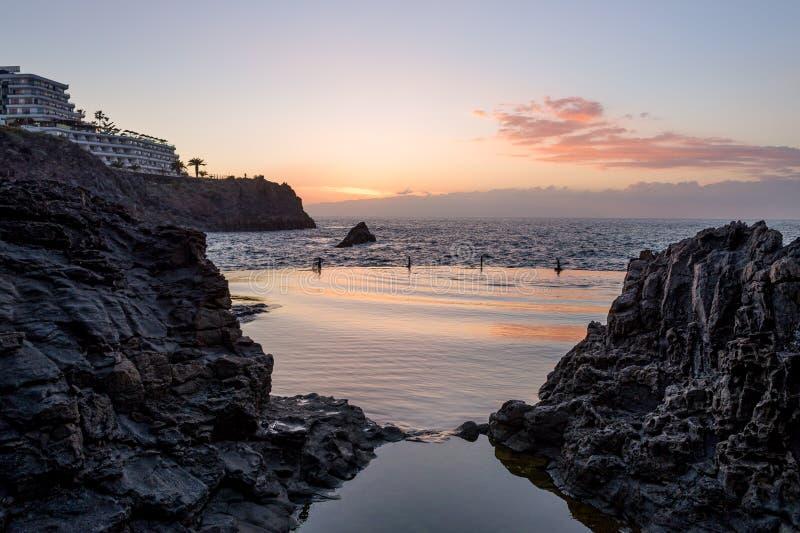 Zonsondergang bij lavabassin - Piscina Naturale in Puerto Santiago stock foto's