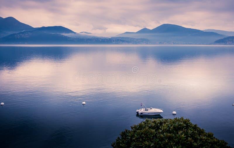 Zonsondergang bij meer maggiore met bergen en motorboot royalty-vrije stock foto's