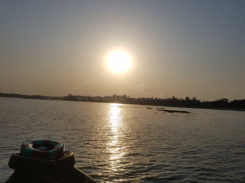 Zonsondergang bij meghnarivier stock afbeelding