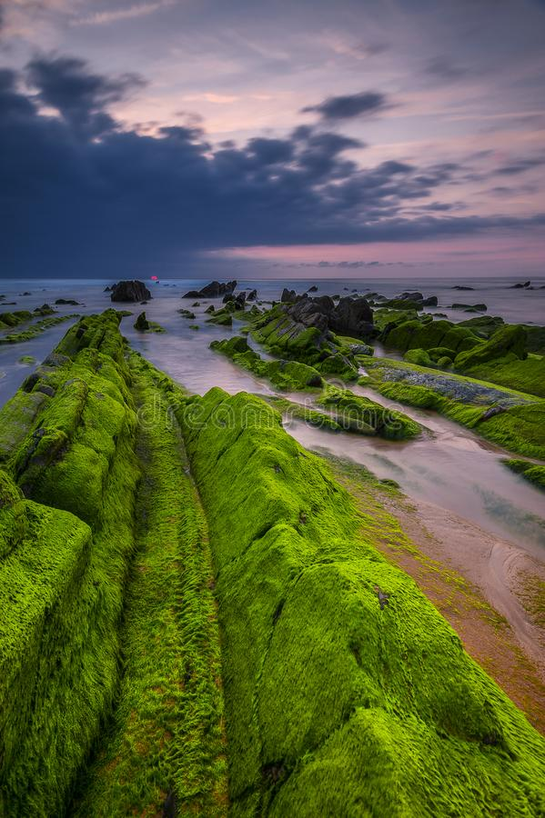 Zonsondergang bij rotsachtig strand royalty-vrije stock fotografie