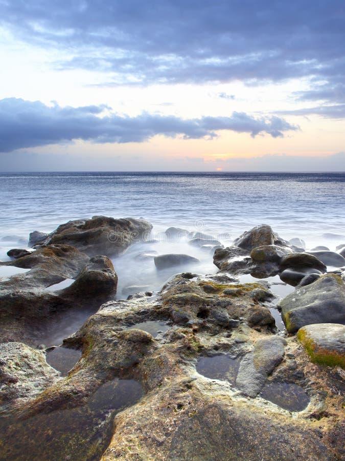 Zonsondergang bij rotsachtig strand royalty-vrije stock afbeelding