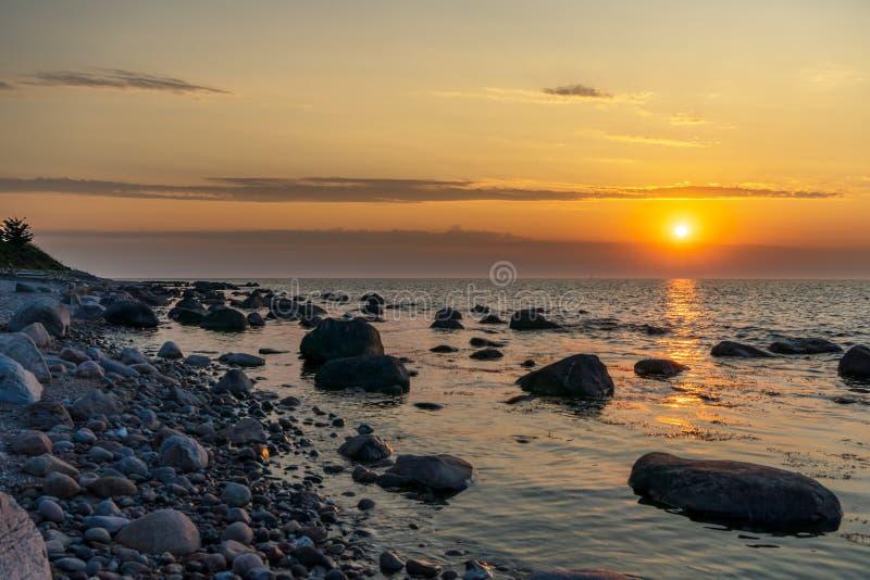 Zonsondergang bij steenachtig strand royalty-vrije stock afbeeldingen