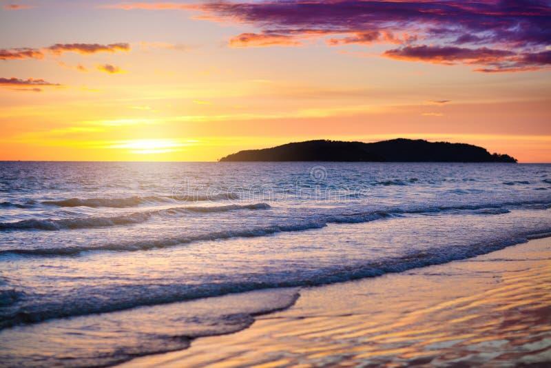 Zonsondergang bij tropisch strand Oceaangolven door zonsopgang royalty-vrije stock afbeeldingen