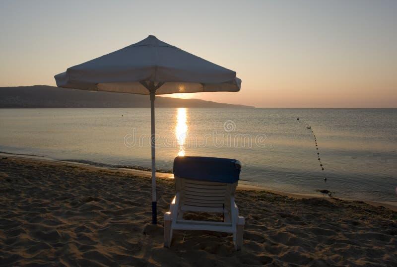 Zonsondergang, chaise en paraplu stock afbeelding