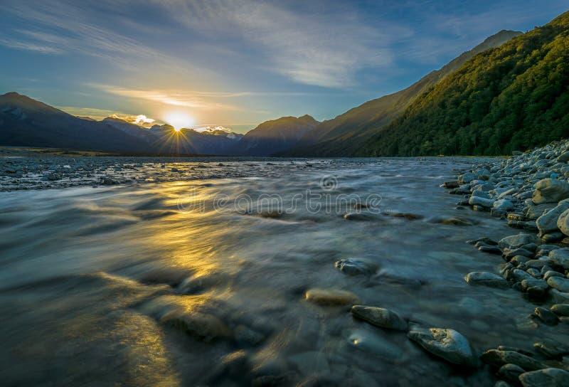 Zonsondergang in de Bergen met de rivier die, Nieuw Zeeland voorbij stromen stock foto's