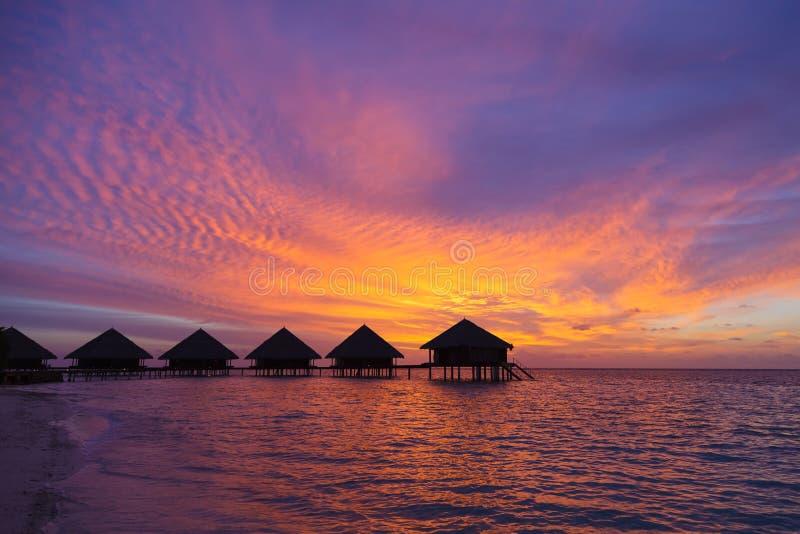 Zonsondergang in de Maldiven met een mening van de lagune en de bungalowwen royalty-vrije stock afbeeldingen