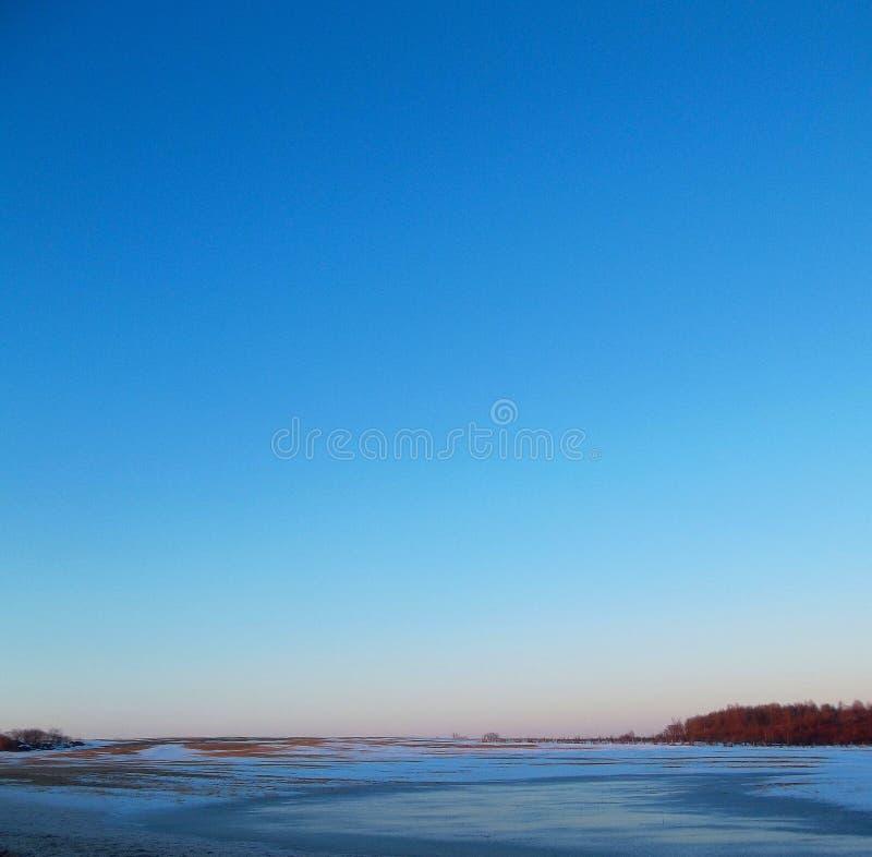 Zonsondergang in de winter over een ijzig gebied royalty-vrije stock afbeeldingen