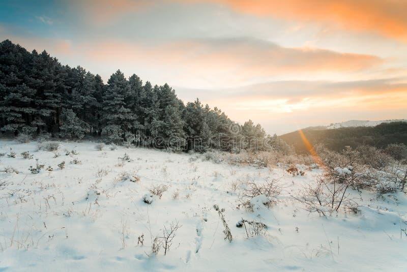 Zonsondergang in de winterbergen stock afbeeldingen