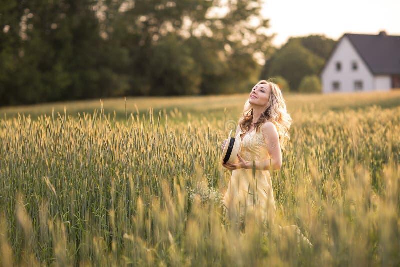 Zonsondergang in de zomer Het landelijke Leven Een jonge vrouw op het gebied werpt een hoed Rustieke stijl stock afbeelding