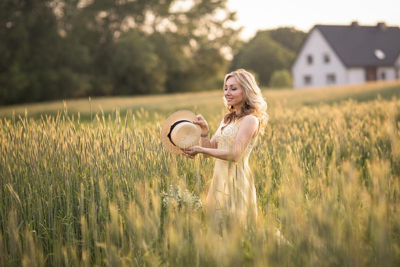 Zonsondergang in de zomer Het landelijke Leven Een jonge vrouw op het gebied werpt een hoed stock fotografie