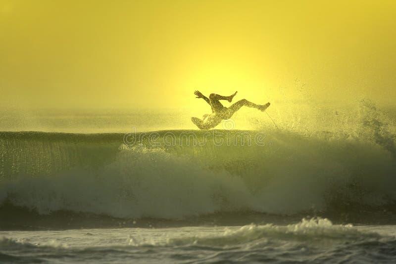 Zonsondergang die surfer valt stock afbeelding