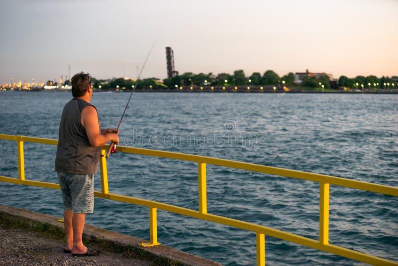 Zonsondergang die van een pijler vissen stock foto's