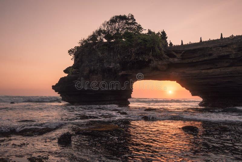 Zonsondergang door van rotsachtige klip op kust bij zonsondergang Pura Batu Bolong, Bali royalty-vrije stock foto's
