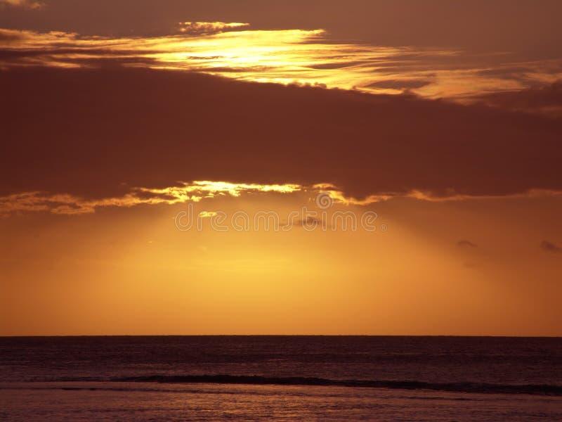 Zonsondergang door wolken stock fotografie