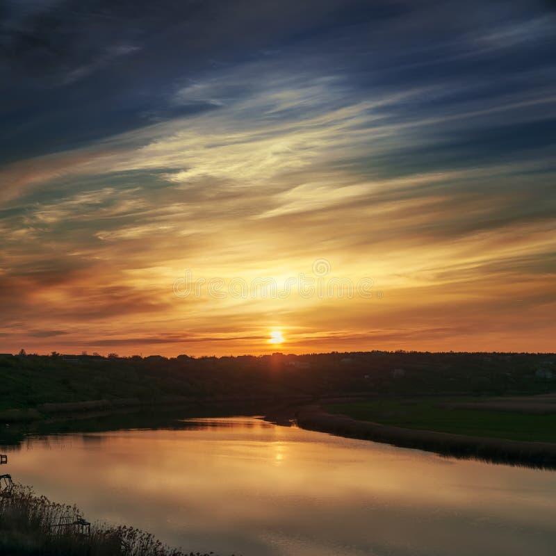 Zonsondergang in dramatische wolken over rivier stock fotografie