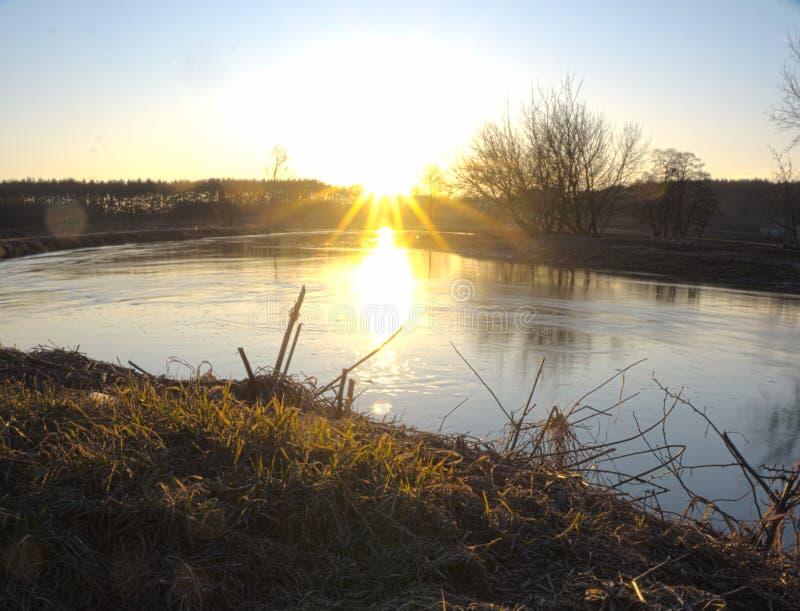 Zonsondergang in een de herfst wolkenloos weer Een schone rivier met rollende zonnestralen stock afbeelding