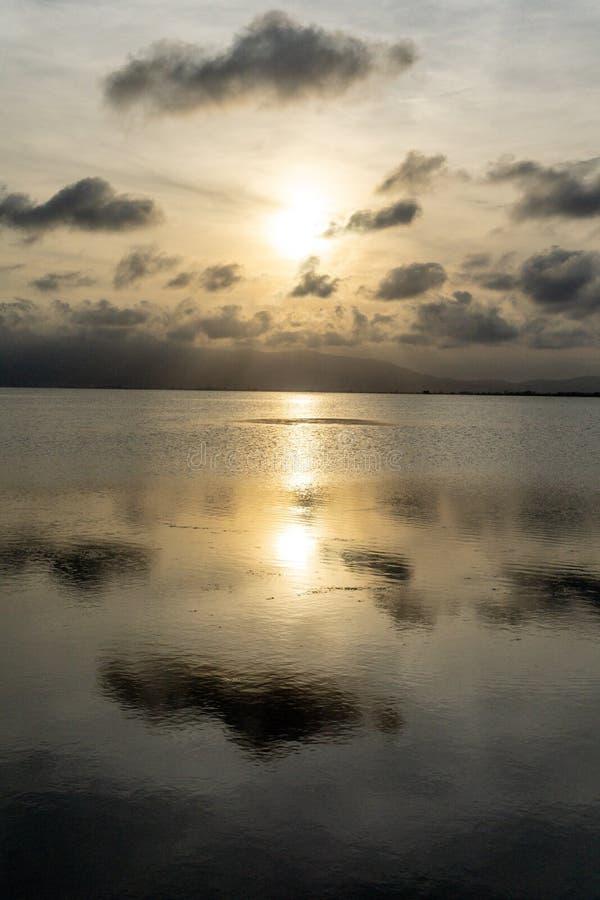 Zonsondergang in een kalme overzees met mooie wolken stock afbeeldingen
