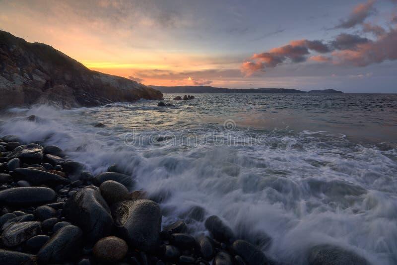Zonsondergang in een rotsstrand royalty-vrije stock foto