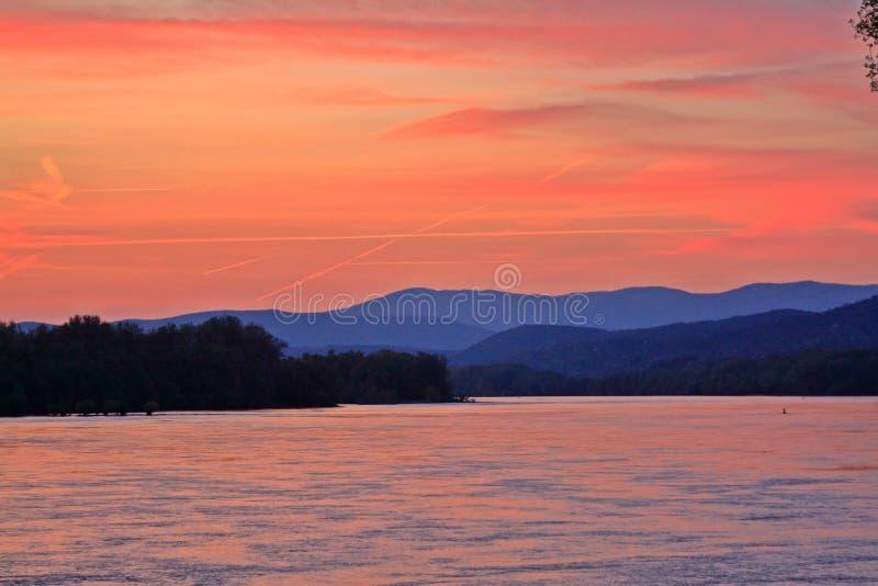 Zonsondergang en bergen boven de Donau stock foto
