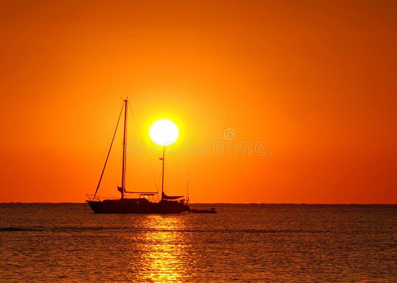 Zonsondergang en boot stock afbeeldingen