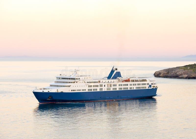 Zonsondergang en de blauwe veerboot in Griekse eilanden stock afbeeldingen