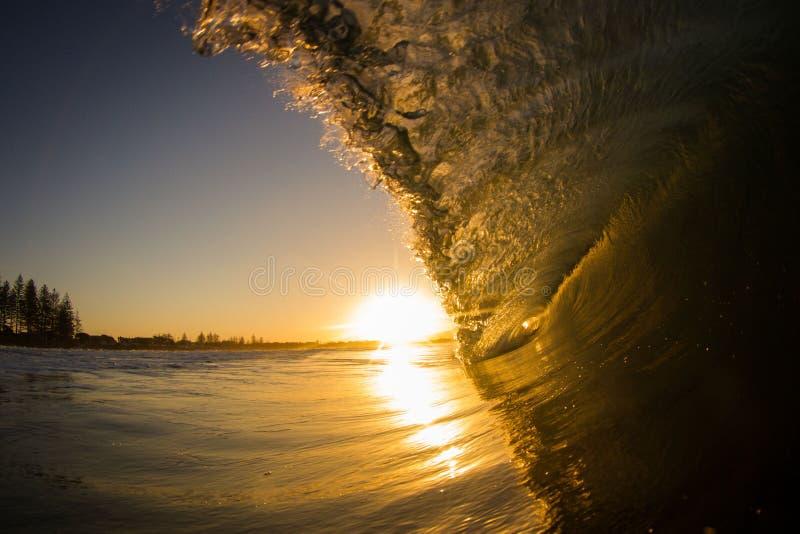 Zonsondergang en de golf stock afbeeldingen
