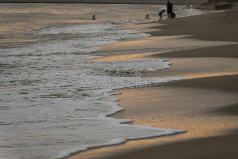Zonsondergang en de schuimende golven die patronen op de de zonsonderganggradiënt van de strand sterke avond maken royalty-vrije stock foto's
